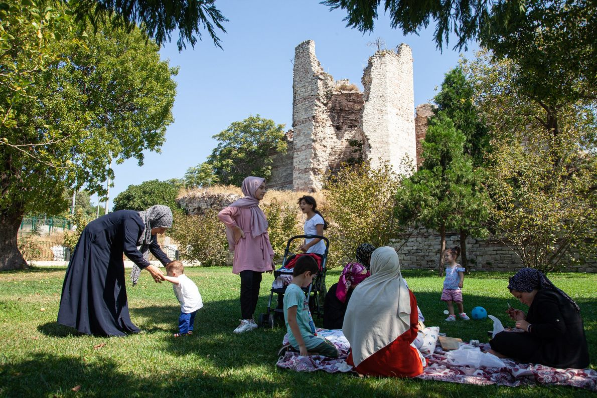 A family enjoys a picnic in the shadow of the crumbling Theodosian walls, which protected the ...