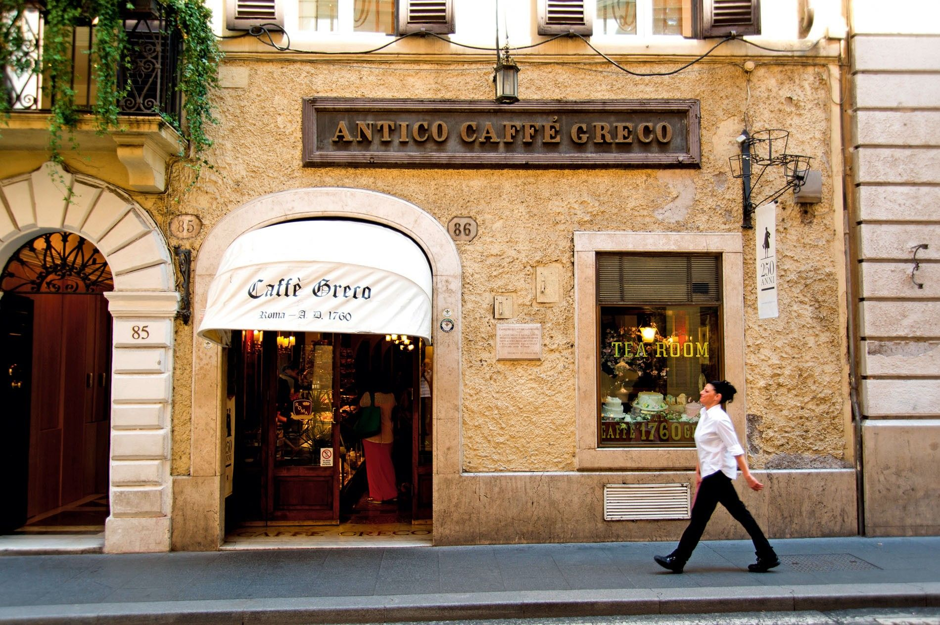 Waiter walking past Antico Caffe Greco, Rome