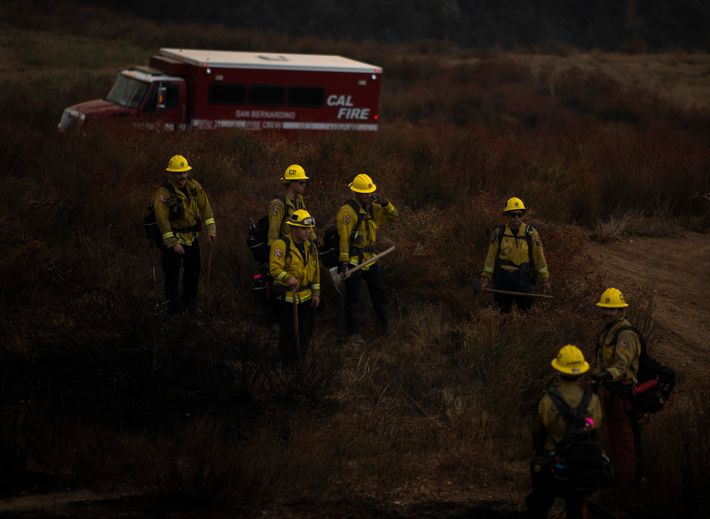 Covered in ash and dirt, a CAL FIRE crew takes a break after a day spent ...