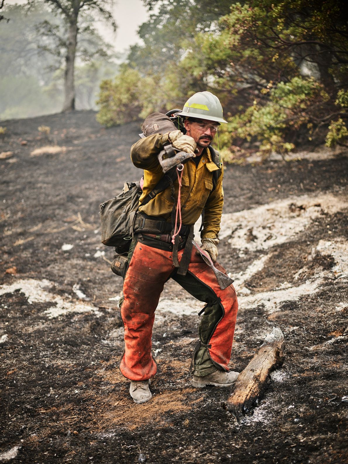 A member of the Dust Busters fire crew from Oregon works along Stringtown Road in Oroville, ...