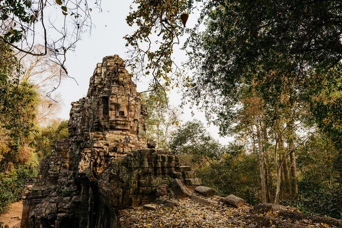 Deep in the forest and enclosed by a moat, the vast Angkor Thom complex surrounding Bayon ...
