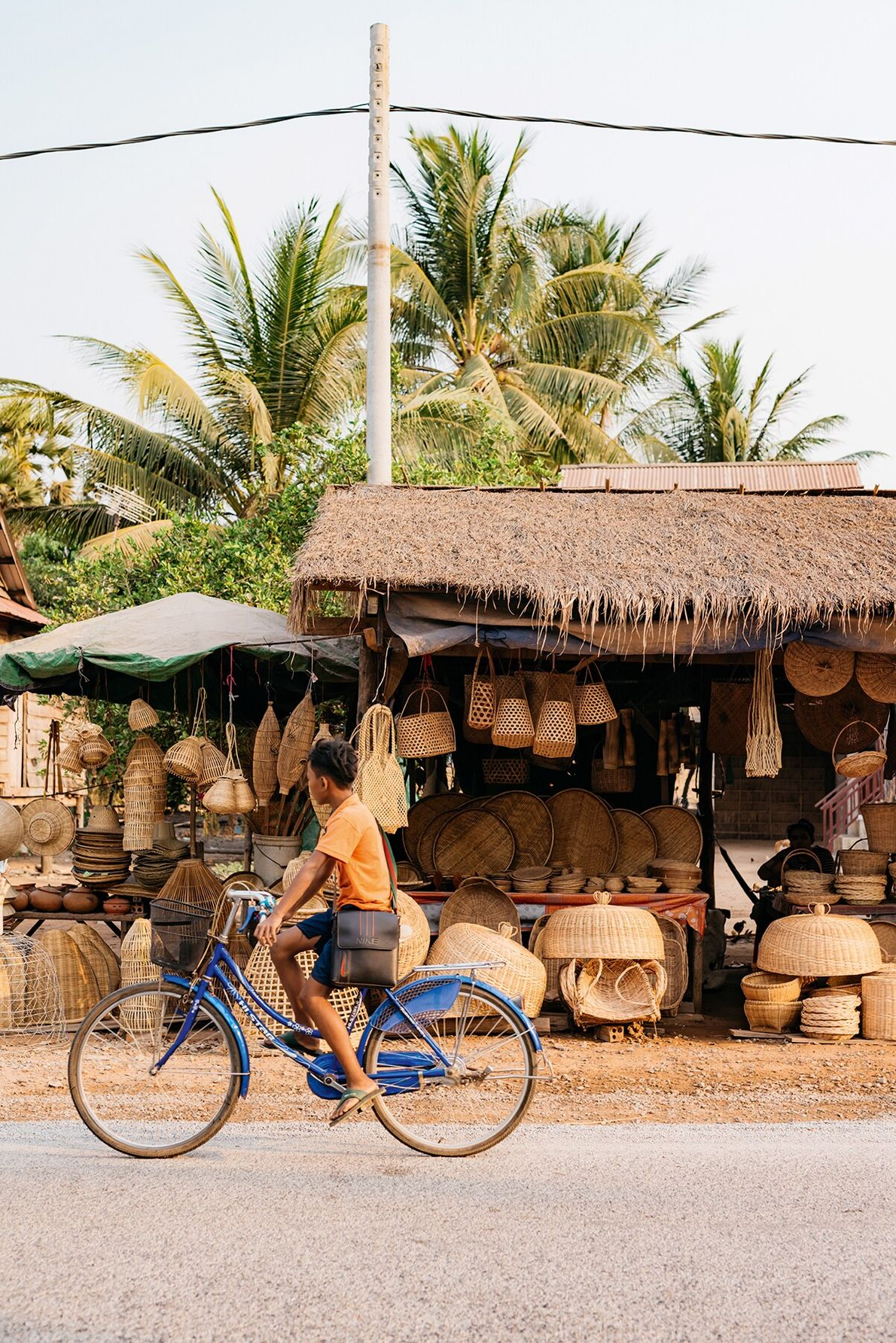 Vendors, from basket weavers to fruit sellers, tout their wares on the roadside at Preah Dak, ...