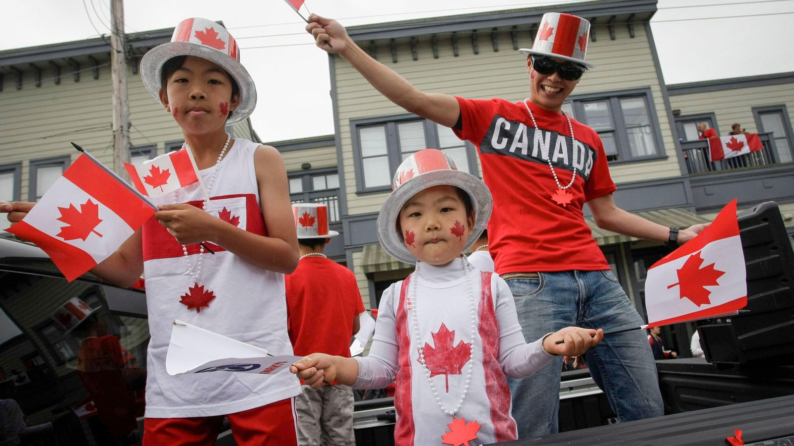 Local residents wave the national flag of Canada during the 73rd Salmon Festival Parade in Richmond, ...