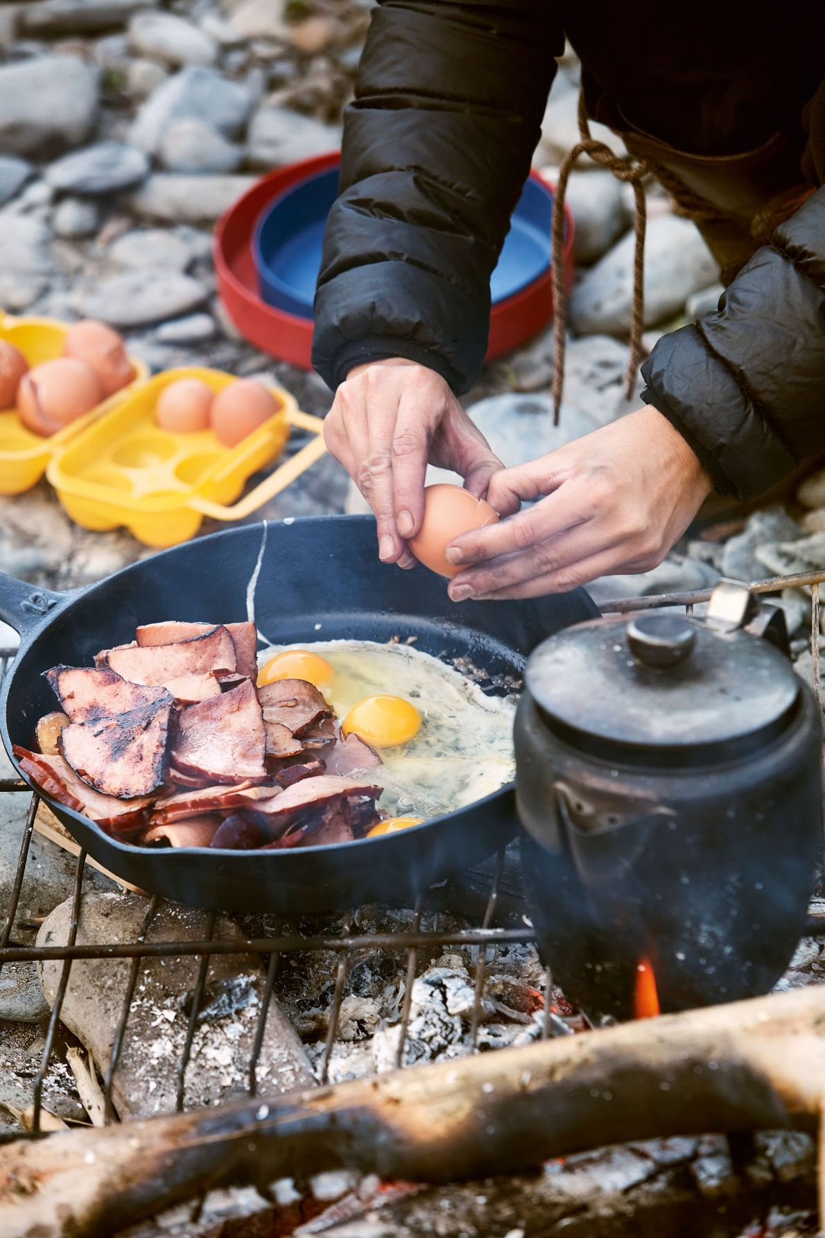 A hearty Canadian campfire meal of bacon rashers with maple syrup and fried eggs.