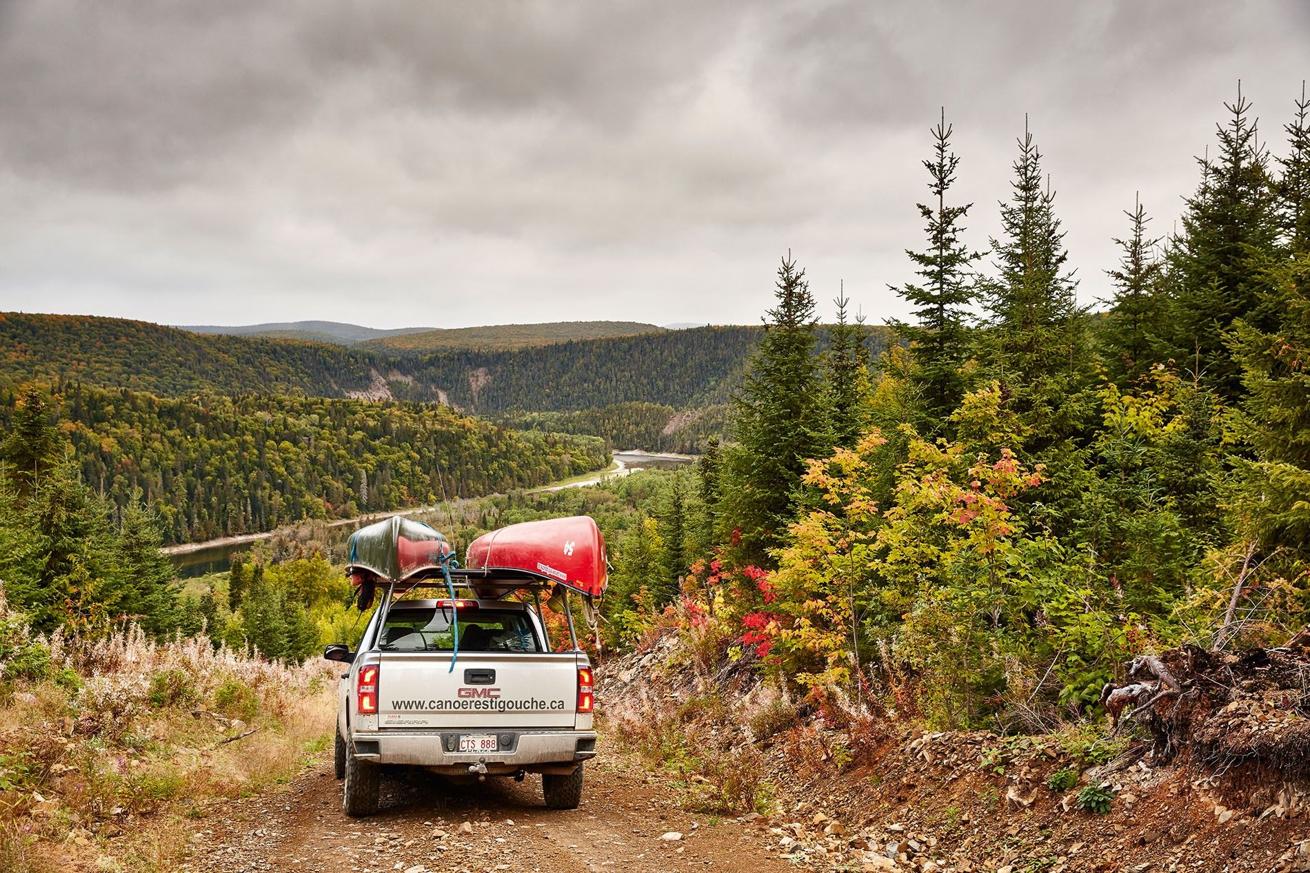 Packing canoes onto a four-wheel-drive vehicle, as clouds draw in across the pristine wilderness.