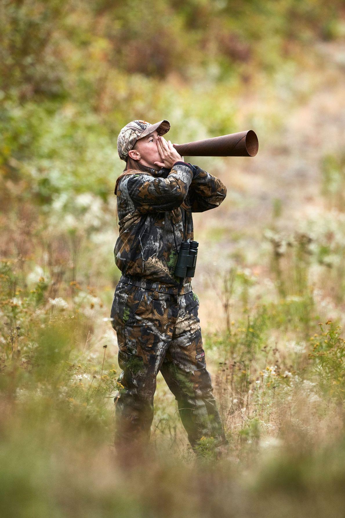 Nancy Boucher, a moose caller, mimics moose calls amplified through a cone.