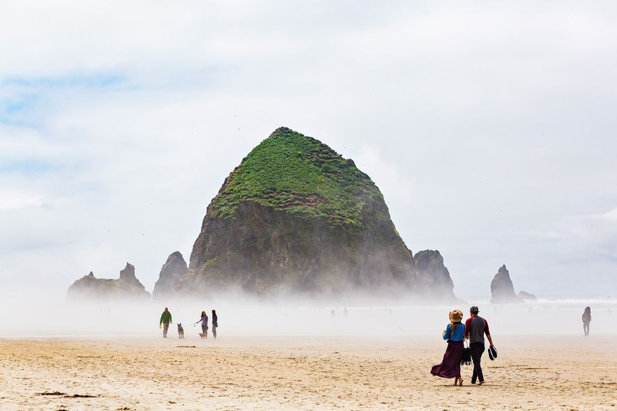 Mist fills Cannon Beach, Oregon, but that does not stop visitors from enjoying a walk.