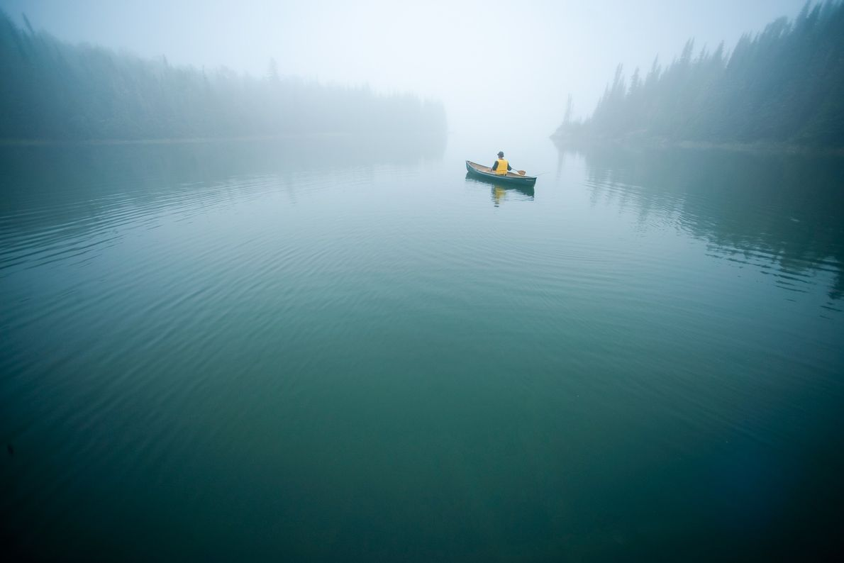 Canoeist paddles the quiet and protected inside passage within the Slate Islands on Lake Superior, in ...