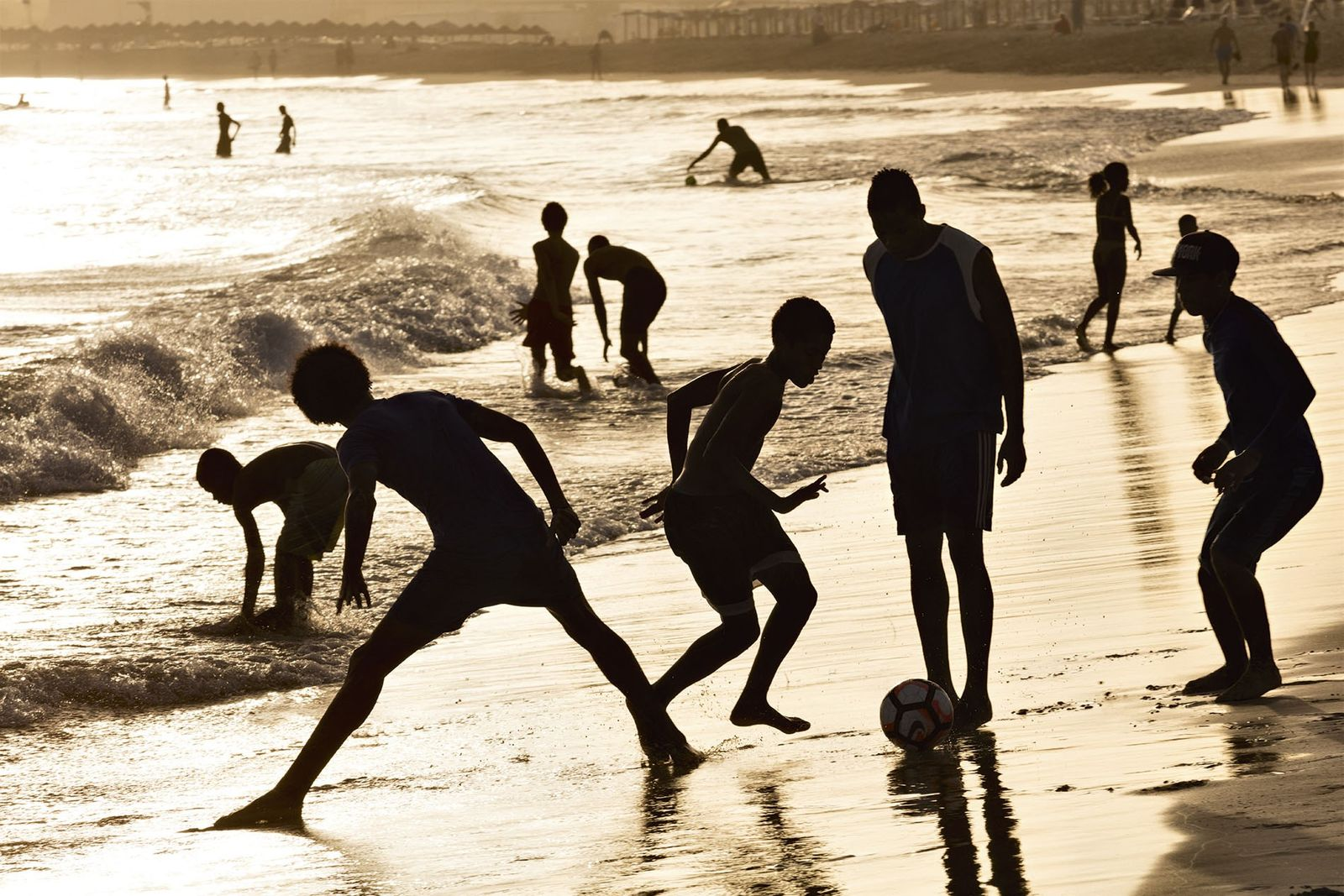 Playing football in the waves.