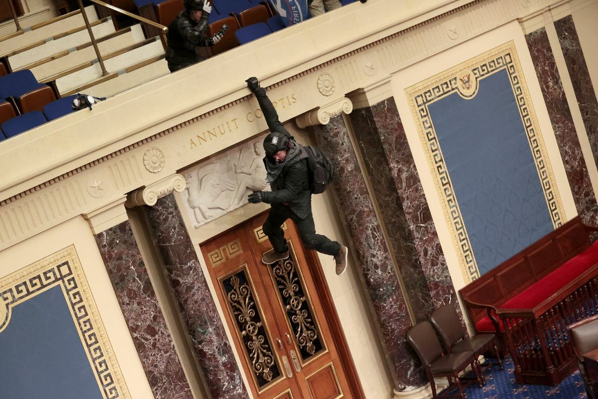 A Trump supporter is seen hanging from the balcony in the Senate Chamber.