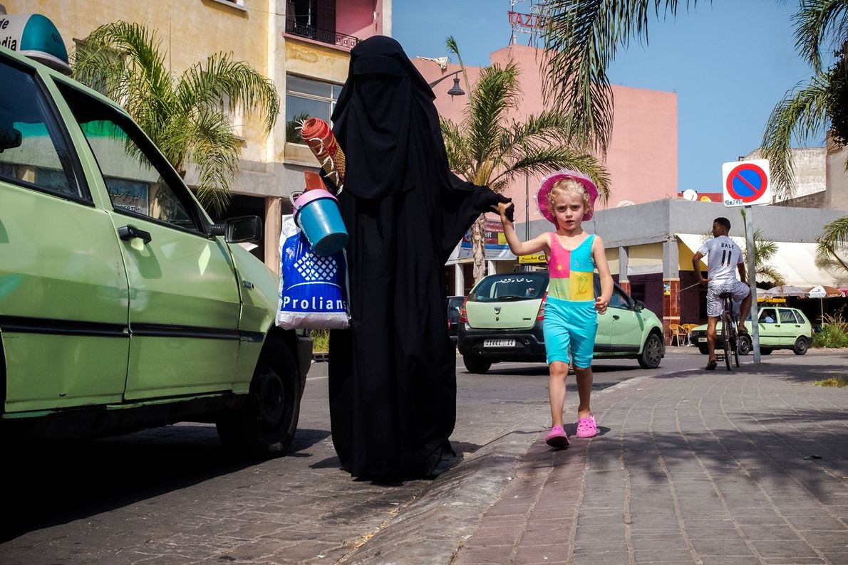 Colourful clothes of a young girl contrasts with her companion's burka. Most Moroccans are Sunni Muslims, ...