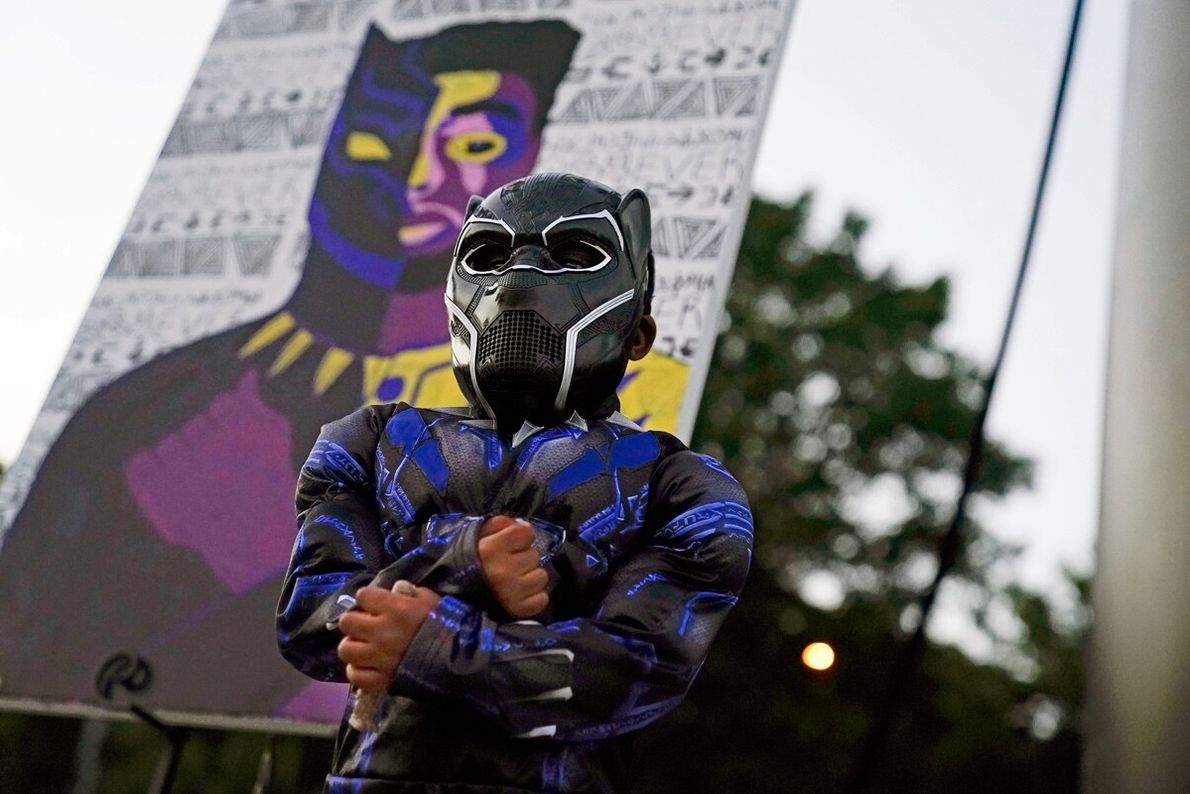 Four-year-old Mason Wilkes poses in a Black Panther costume in front of a painting during a ...