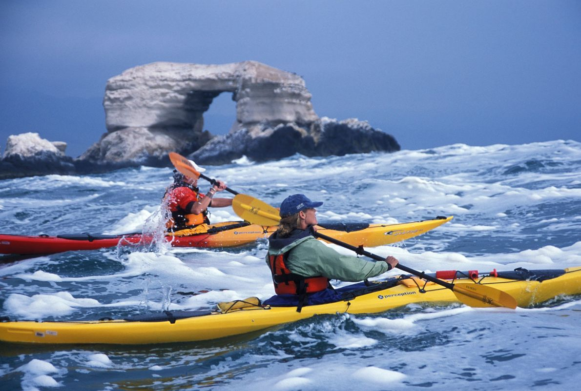 Two kayakers paddle past La Portada, a natural archway off the coast of Antofogasta in northern ...