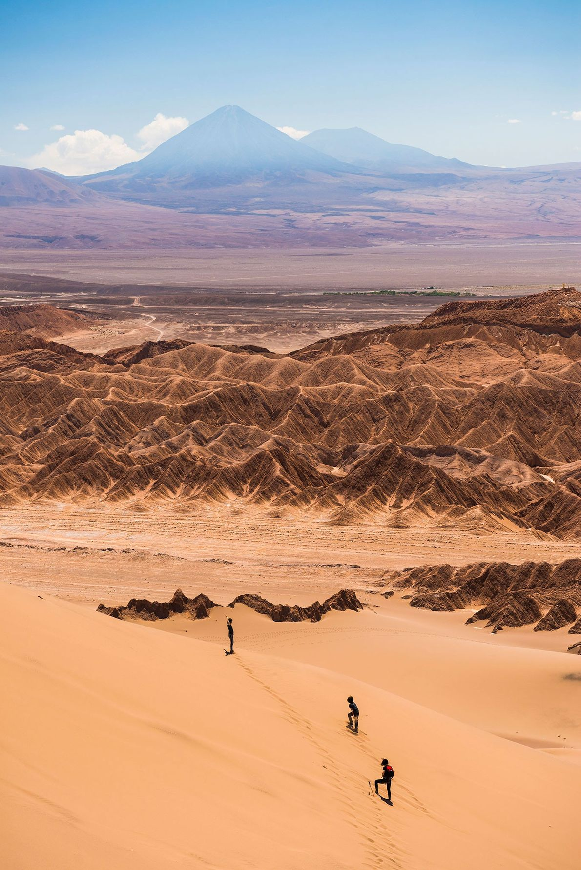 Hikers walk across the Valley de la Muerte sand dunes in Chile's Atacama Desert. The valley ...