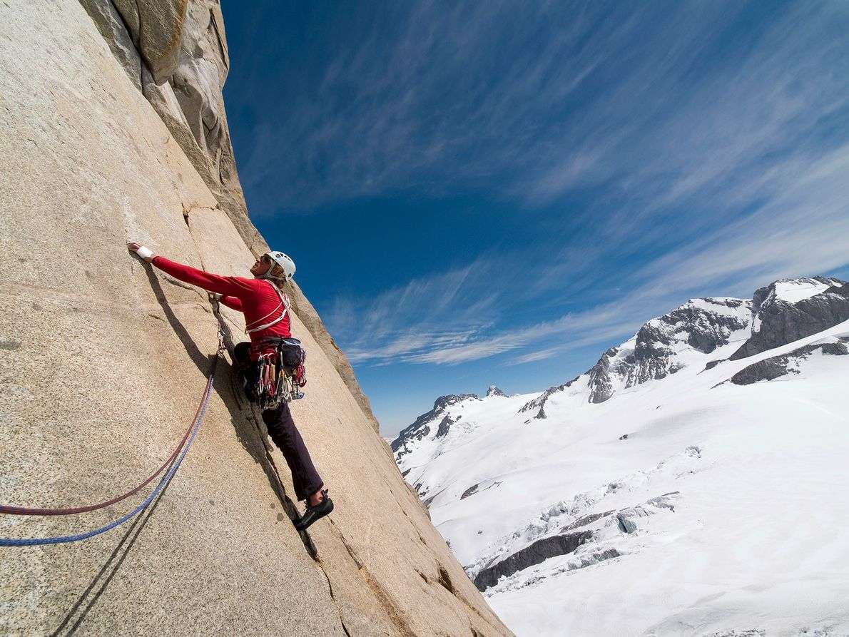 A climber ascends a challenging wall in the Andes Mountains. Alpine, free, and sport climbing are ...