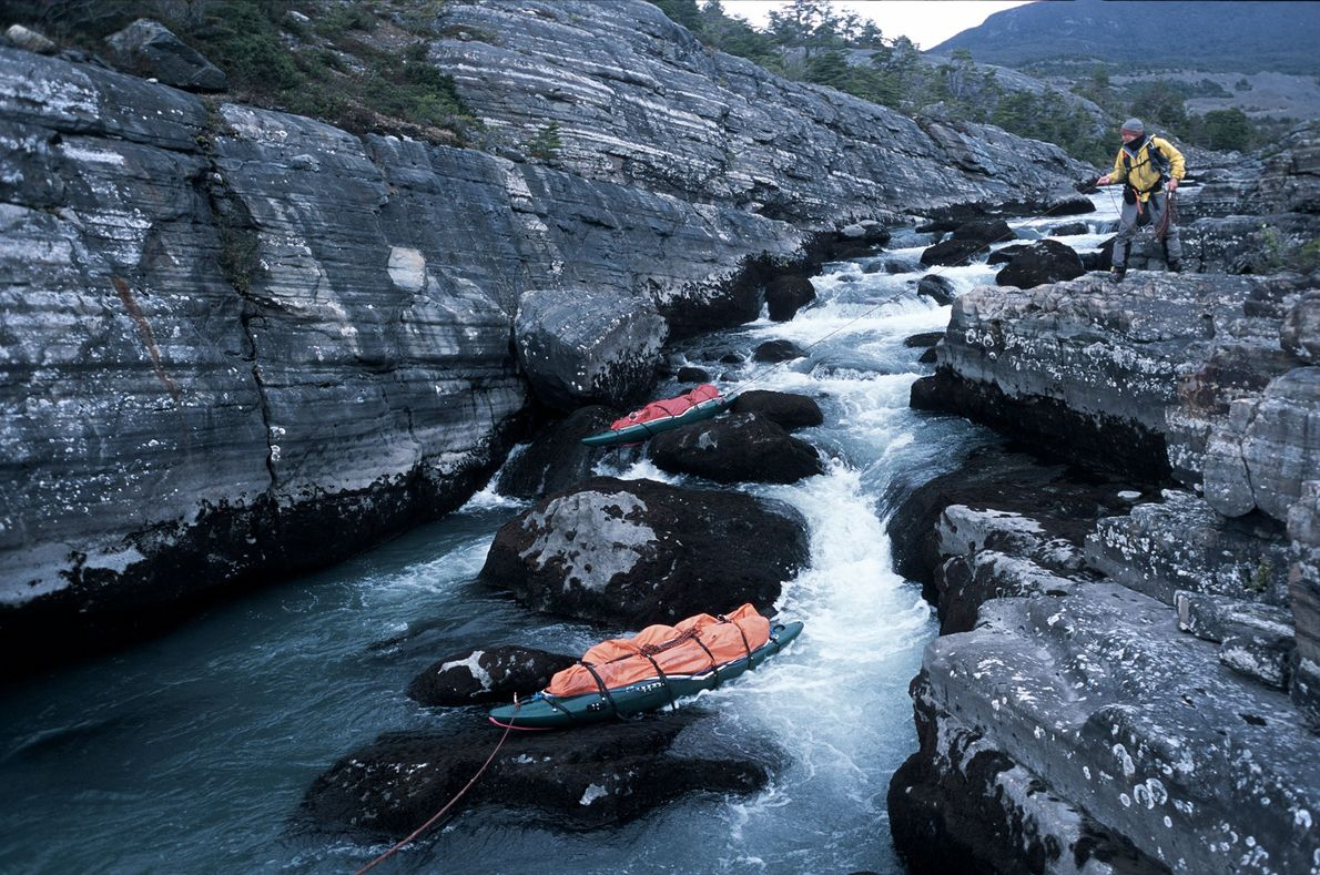 Kayaks loaded with gear sit waiting for paddlers to ride them down the rushing river to ...