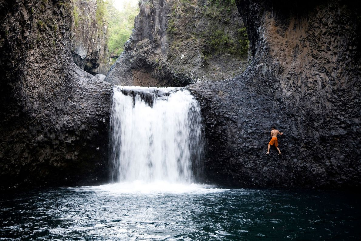 A bold visitor climbs up the rocky side of a small waterfall—one of the falls within ...