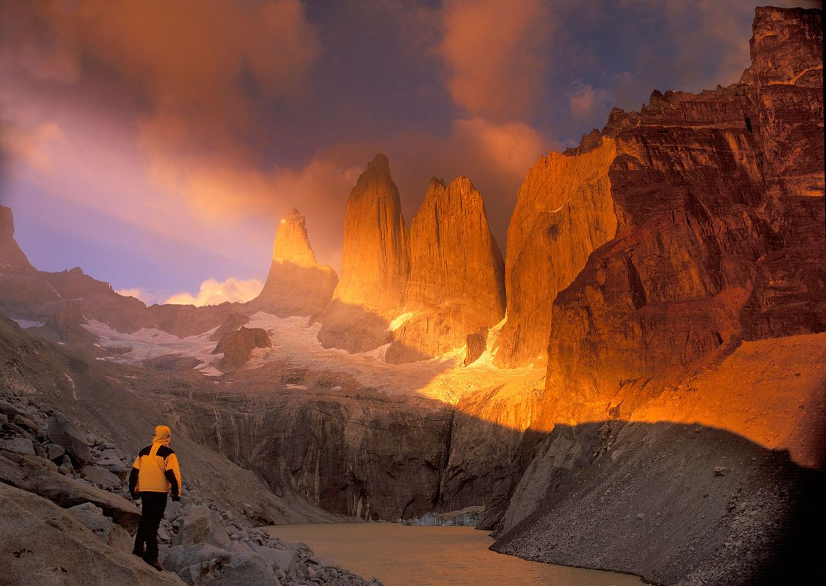 A hiker traverses the rocky landscape of Torres del Paine National Park. Located in southern Chile, ...