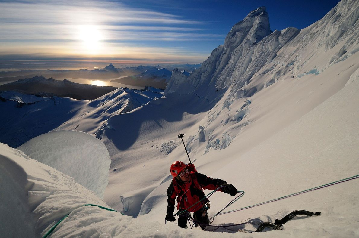 A mountaineer ascends a snowy peak in Tierra del Fuego, a group of islands separated from ...