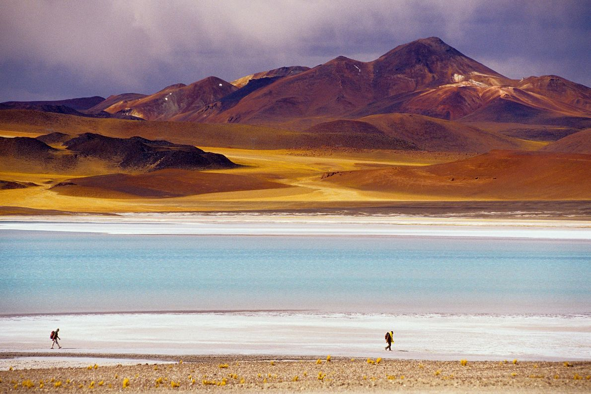 Two hikers travel along the shore of Laguna de Tuyajito in the Atacama Desert, the world's ...