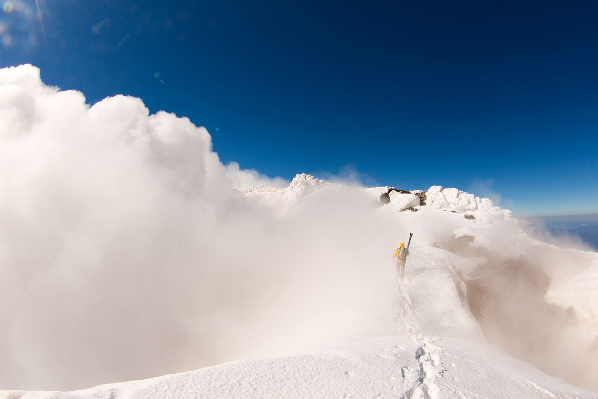 A skier carries his gear through a cloud on a mountain peak in Chile's Lake District. ...