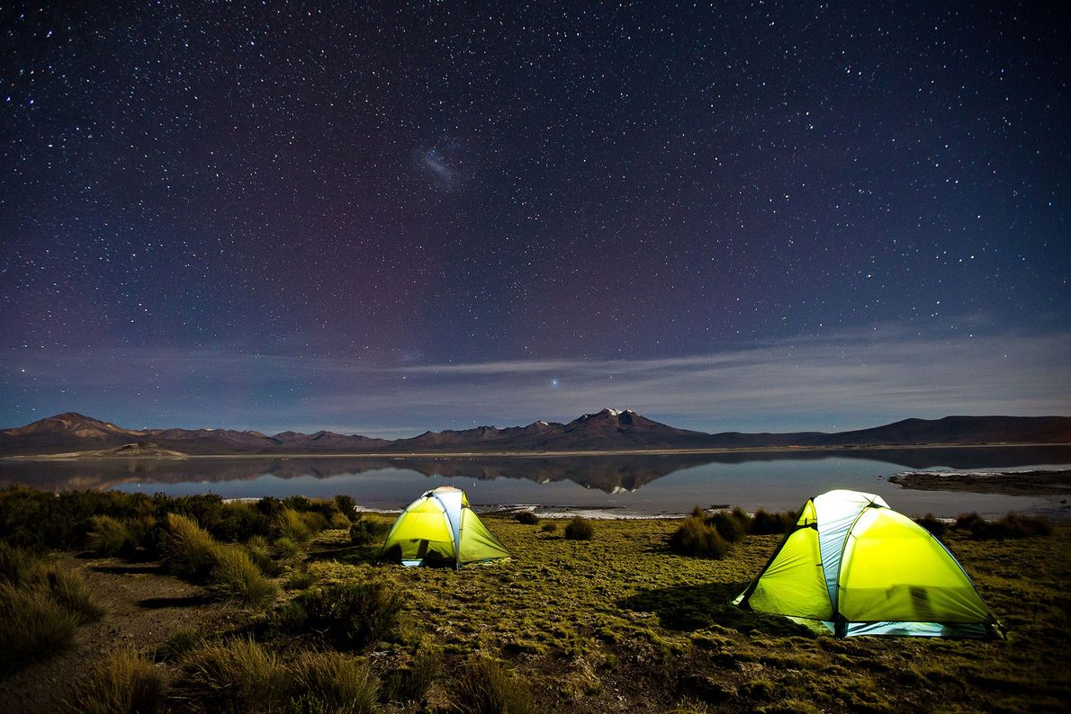 Two tents light up under a starry night sky in Salar de Surire. The Chilean Natural ...