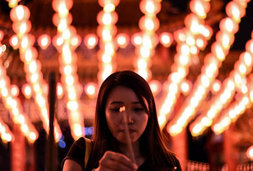A reveler burns joss sticks for incense at Thean Hou Temple in Kuala Lumpur on the ...