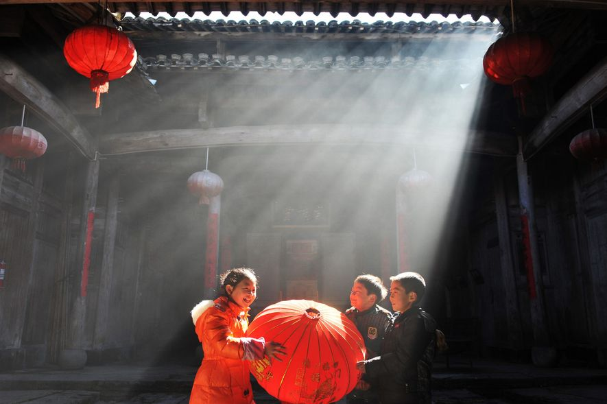 Children help to change lanterns for the upcoming year in an old building of Yangjia village ...