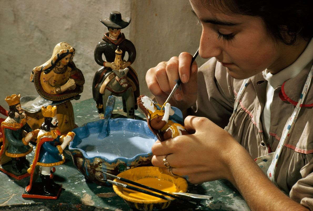 A girl hand-paints nativity figurines in Estremox, Portugal in 1965.