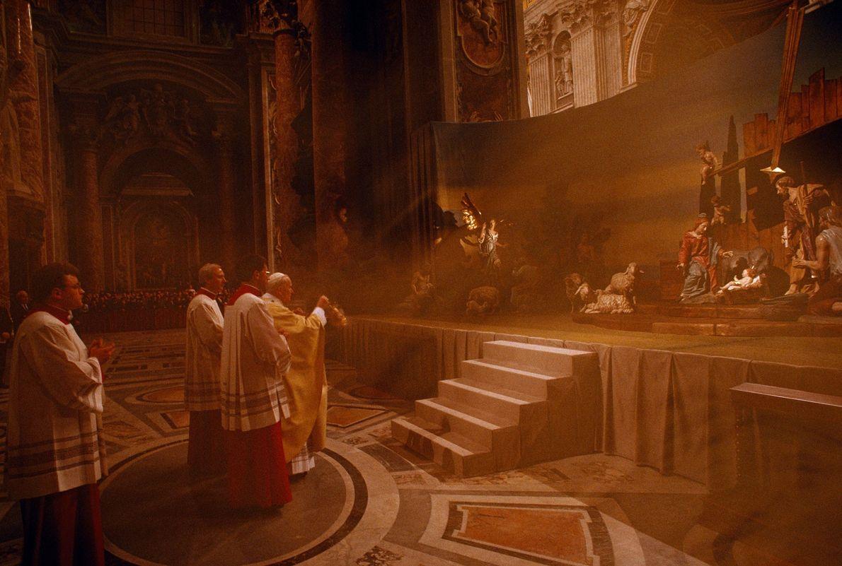 Pope John Paul II coats the nativity scene at St. Peter's Basilica in the Vatican in ...