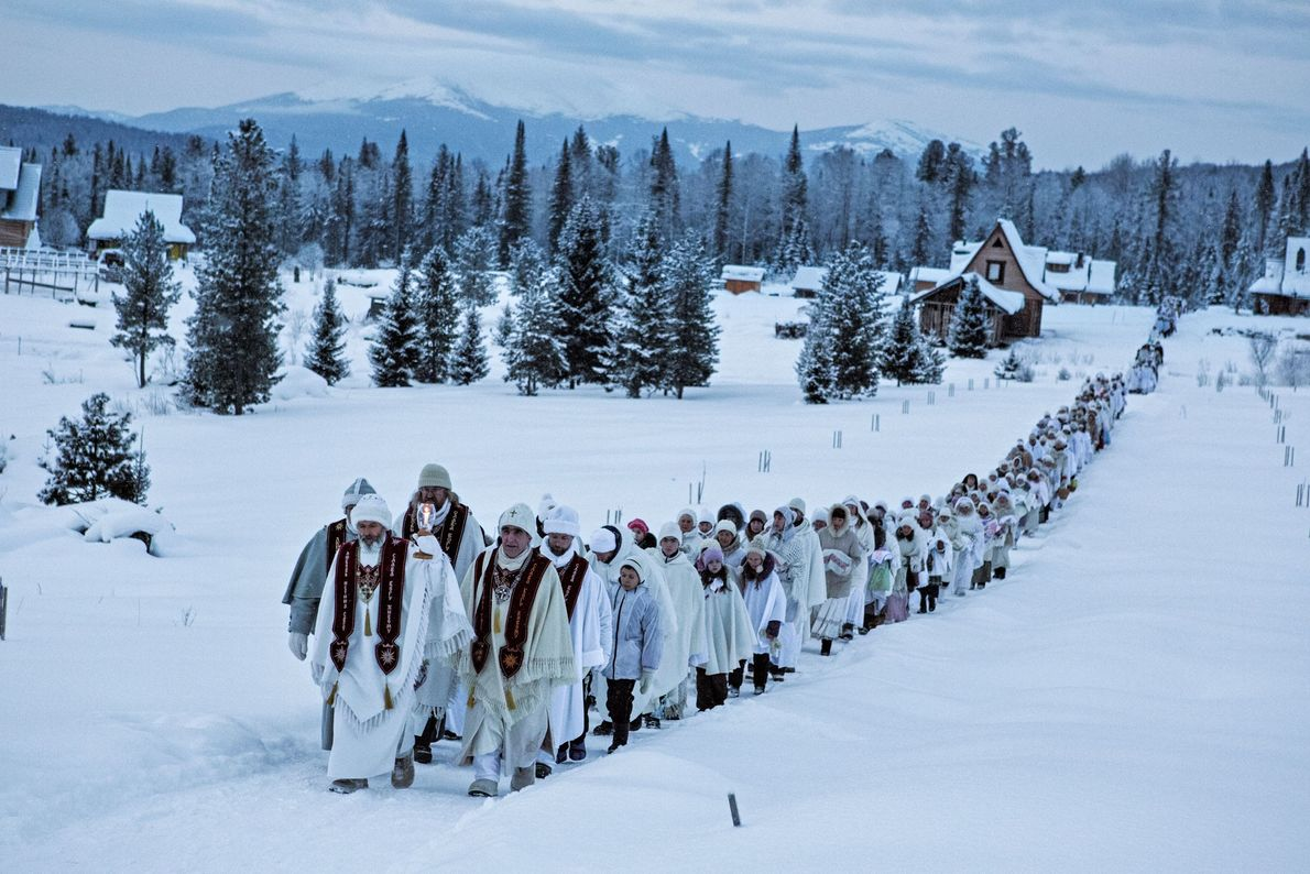 Believers in the Christ of Siberia walk past homes in Cheremshanka while on their way to ...