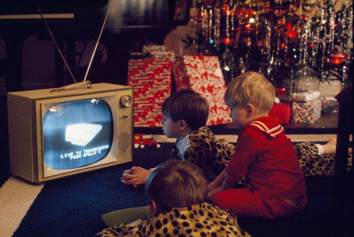 American children are mesmerized by a live transmission from Apollo 8 astronauts in 1968. Watching holiday ...