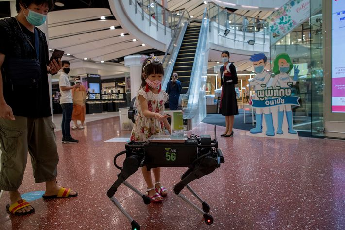 A young girl disinfects her hands with sanitizer dispensed by a robot walking around Central World, ...