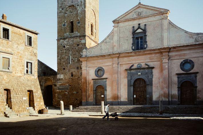 A man pushes a wheelbarrow through Civita's main square in front of San Donato's church. In ...