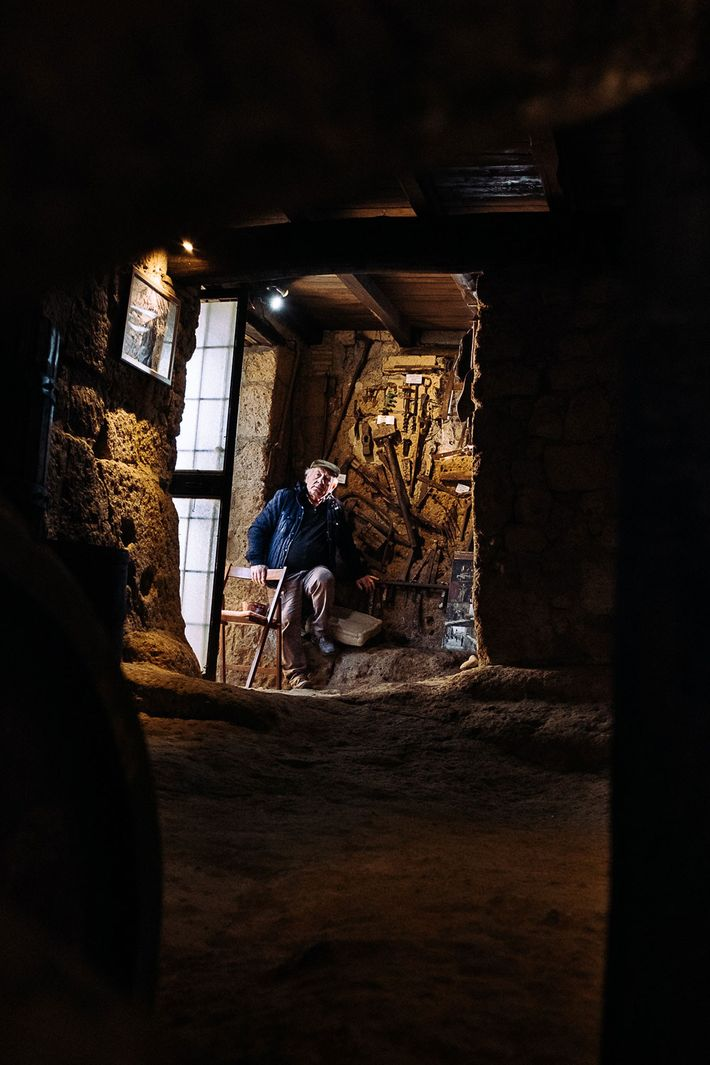 Felice Rocchi, a Civita native, waits in his make-shift museum for tourist. The room is filled ...