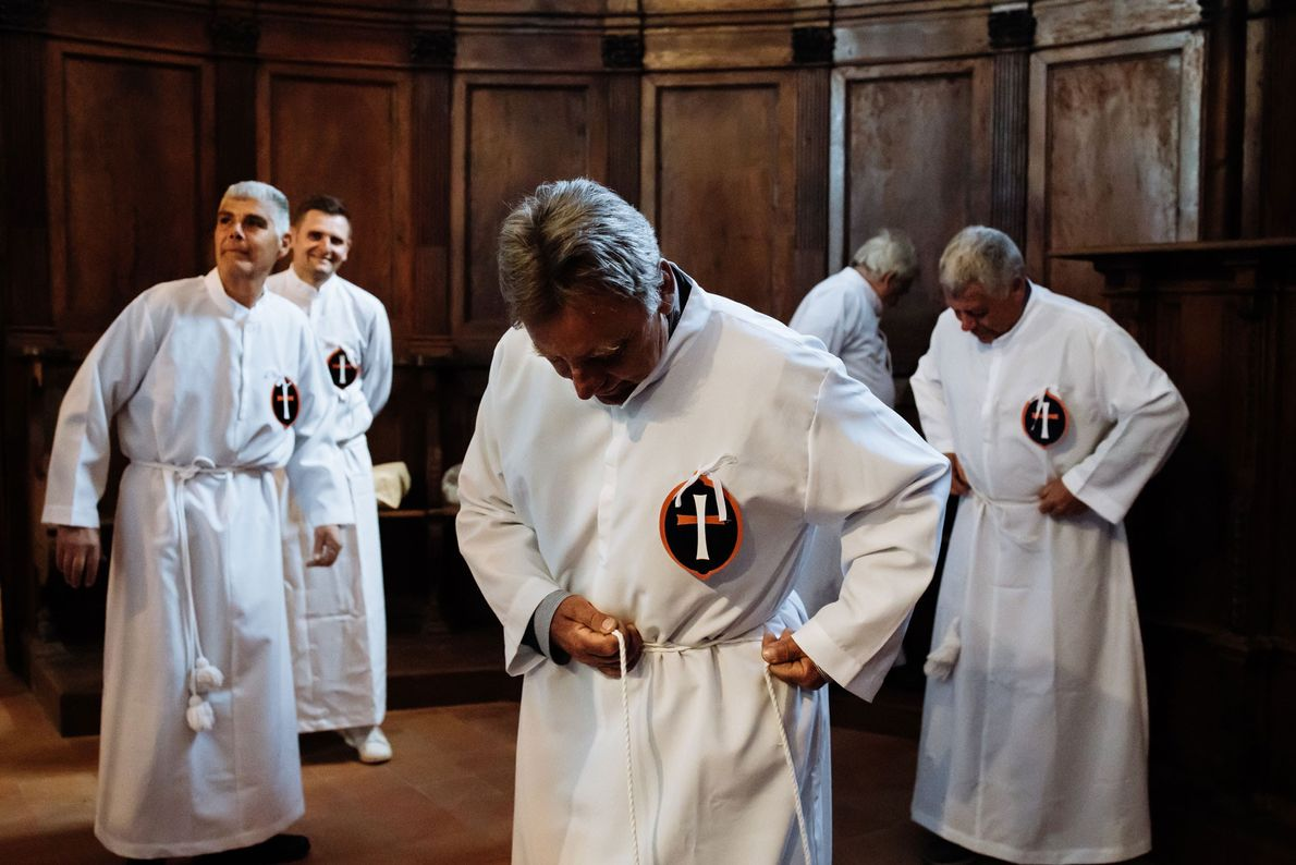 The Confraternity of Civita don their traditional white capes in preparation for the Good Friday mass ...