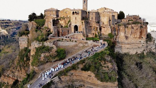 Dressed in white, members of Civita's religious fraternity lead tourists and residents from Civita and Bagnoregio ...