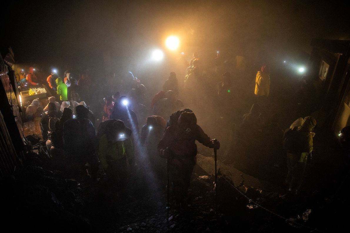 Headlamps pierce the darkness on the final ascent.