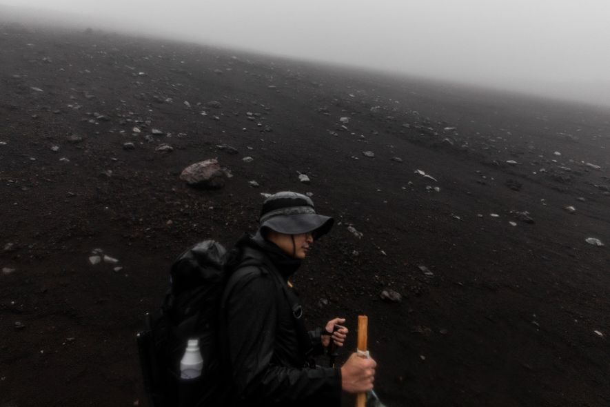A hiker traverses the charred fields of volcanic ash en route to the summit.