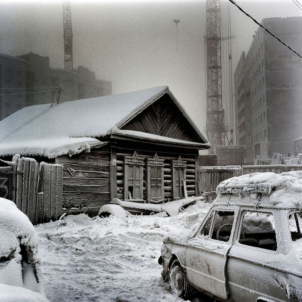A traditional Siberian wooden house is juxtaposed against newer construction. Despite the cold, the economy is ...