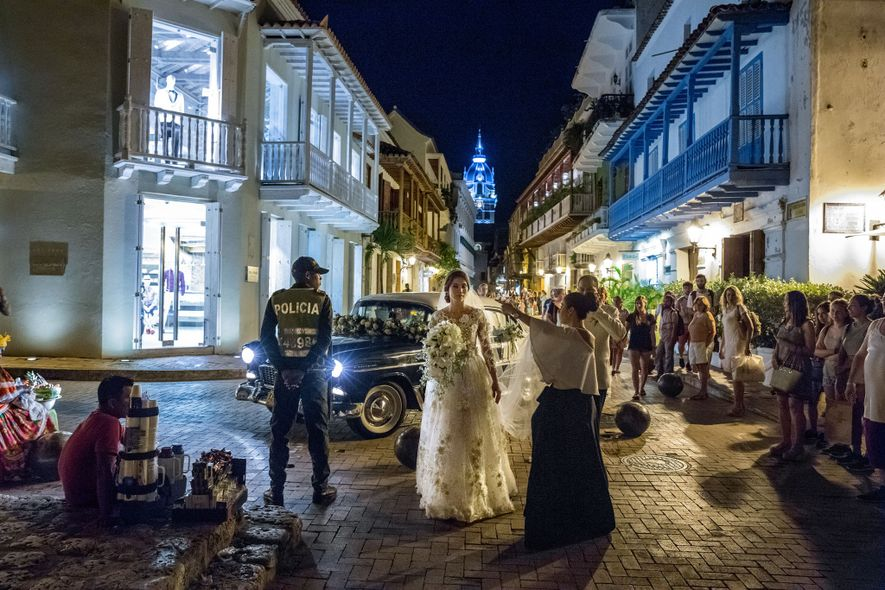 Pedestrians watch a wedding party's arrival at the Church of San Pedro Claver, in the historic ...