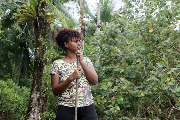 A local woman leans on a hiking stick in the jungle