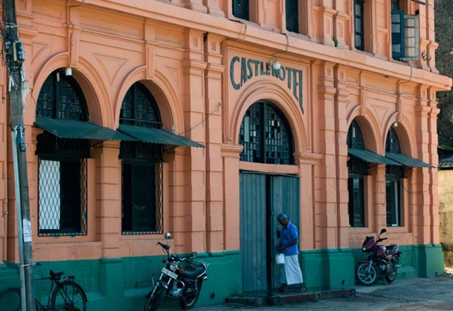 Man standing outside Castle Hotel, Colombo