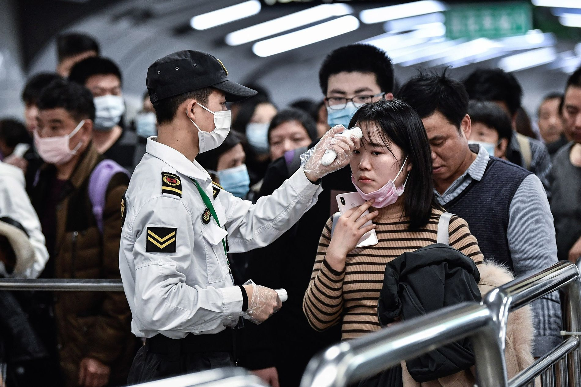 On January 22, citizens in Guangzhou, China, wear masks as they are screened for the new ...