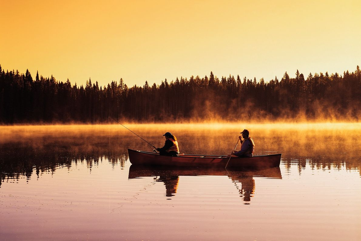 Couple canoeing and fishing in Perch Lake, Duck Mountain Provincial Park, Manitoba.