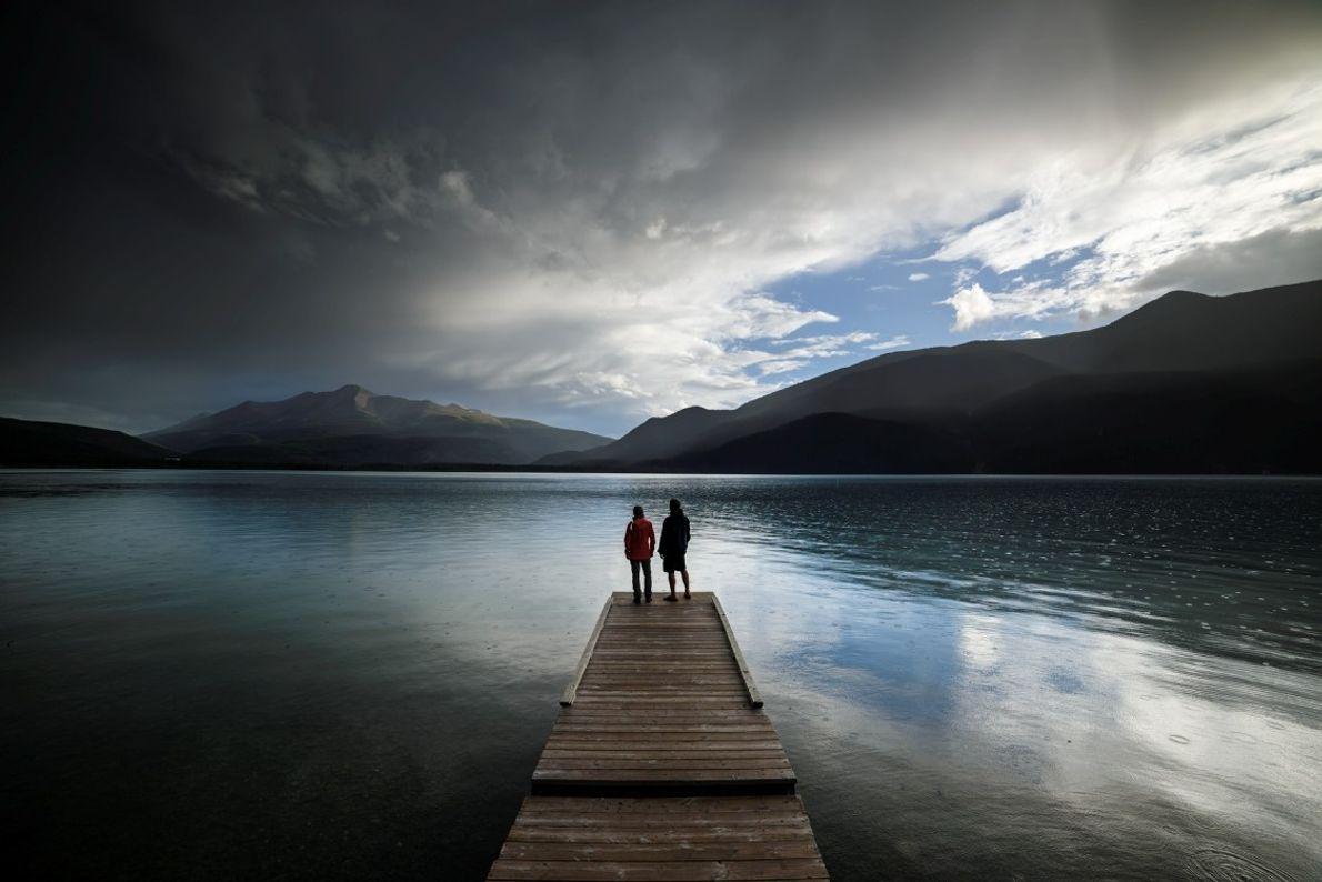 A couple on a pier looking out over Muncho Lake along the Alaska Highway.