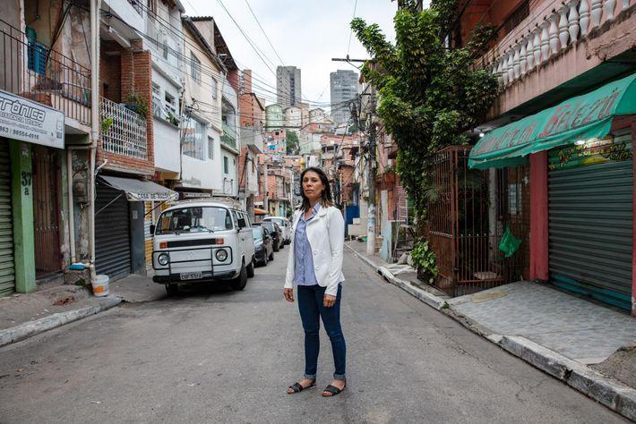 Maria Raimunda Ribeiro de Almeida walks up the steep hills of her favela, Paraisópolis, to meet ...