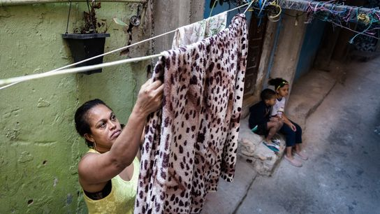 Unemployed domestic worker Ailde de Oliveira Dourado hangs her family's clothes out in the alley. She ...