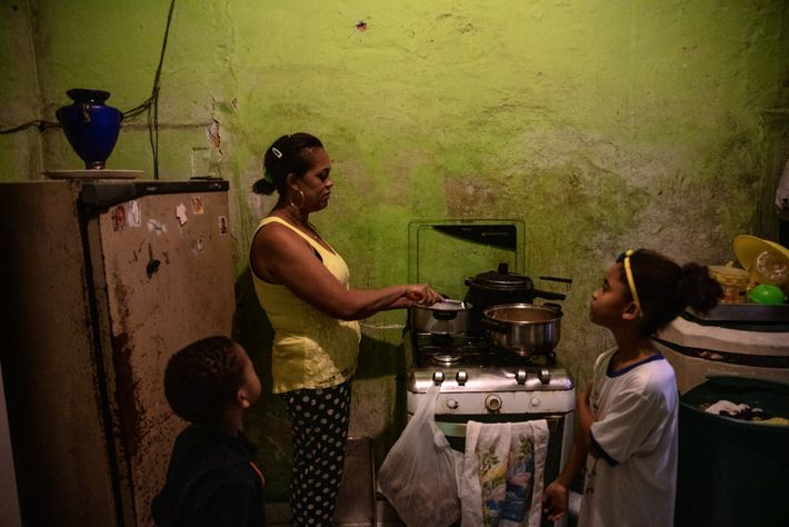 Dourado cooks lunch for her kids, Arthur and Camila, in their home in Paraisópolis. Five-year-old Arthur ...