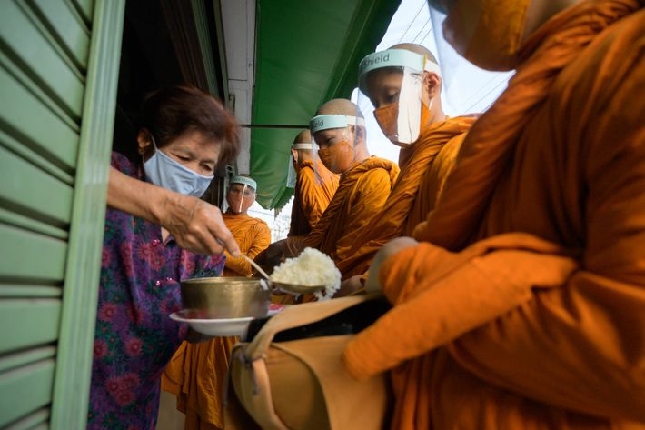 Even during a pandemic, religious practices continue. A woman feeds Buddhist monks, who are not allowed ...